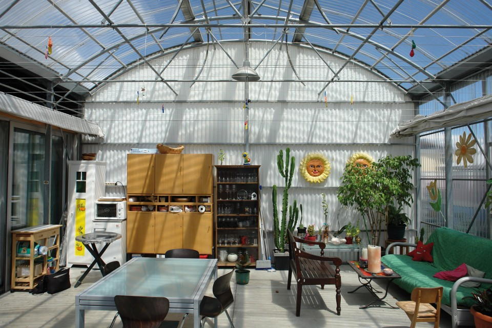 Sala de estar con una mesa, sofá y otros muebles con un techo que recuerda a un invernadero