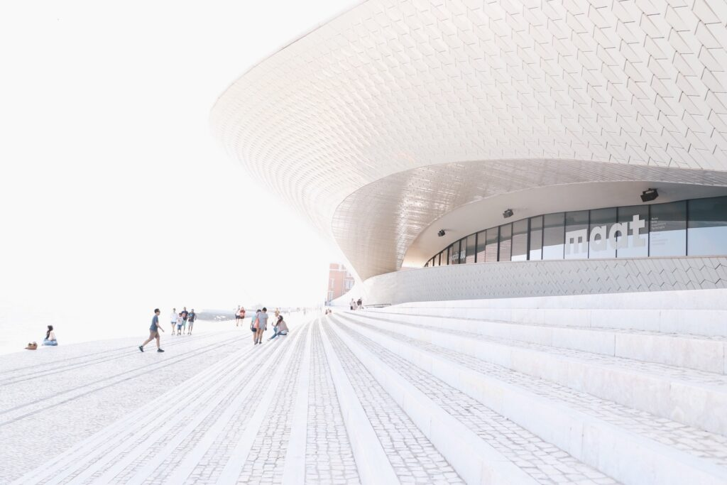 Entrada al edificio con una elegante forma curva y blanca que se inclina hacia delante