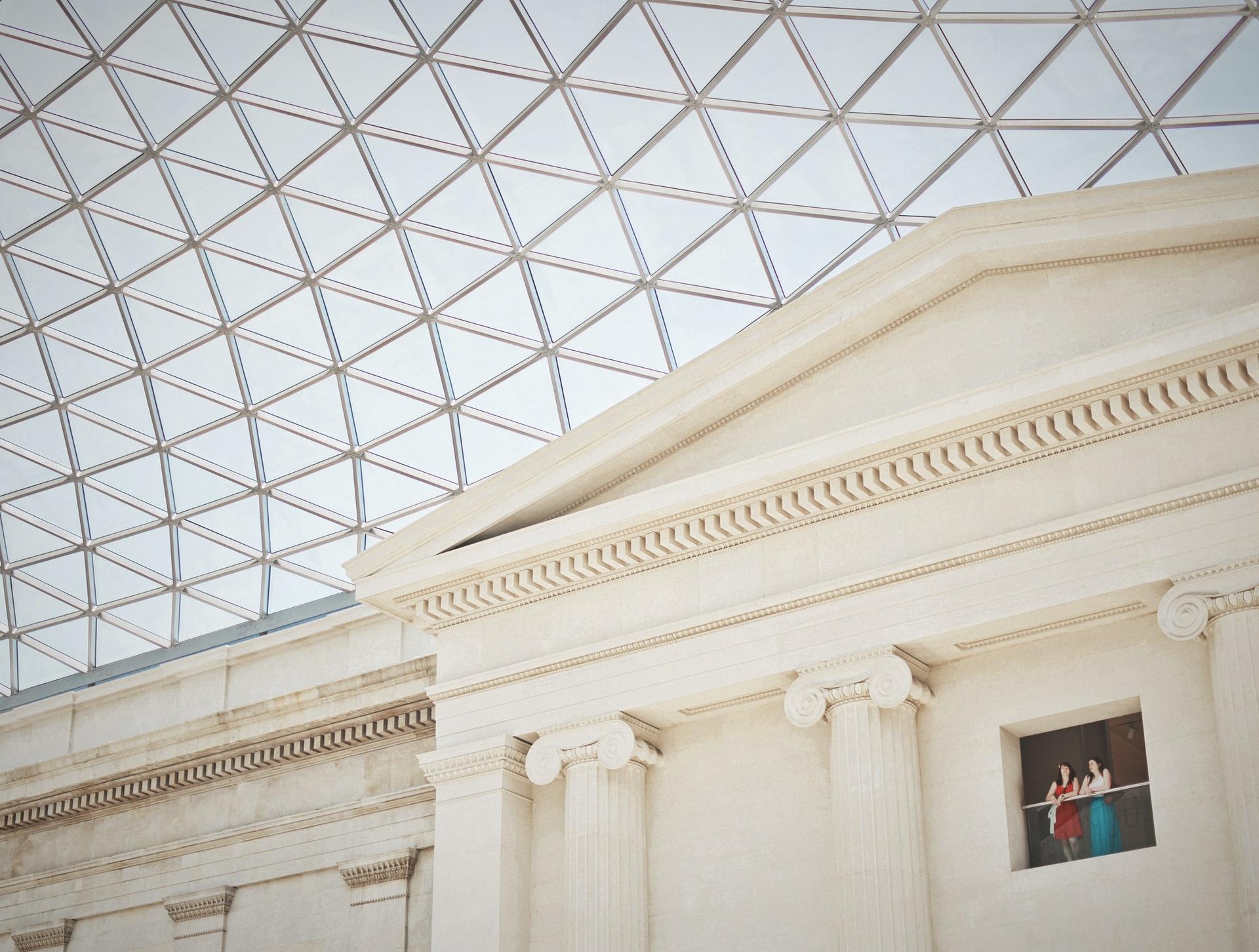 Hall del British Museum. Contrasta el estilo neoclásico de la fachada con un techo que cubre todo el hall construido mediante una estructura metálica triangular y vidrio