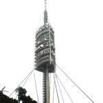 Torre de comunicaciones Collserola. Esbelta torre con varios niveles de los que sobresalen antenas y una serie de cables tensores que la anclan al suelo para mayor estabilidad